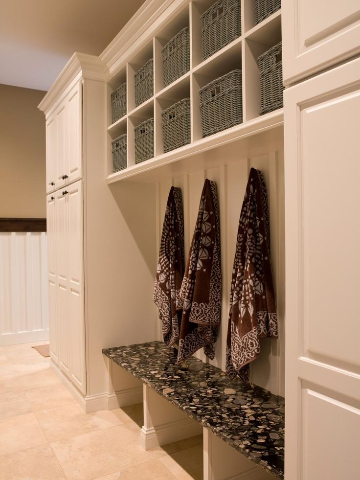 This spacious laundry room is trimmed with white cabinetry, generous storage in matched gray baskets and a cozy seating area.