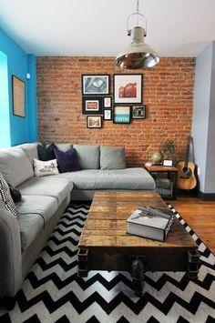 sala de estar decorada com tapete preto e branco com estampa chevron, parede de tijolos a vista com conjuntos de quadros, sofá cinza e mesa de centro de madeira