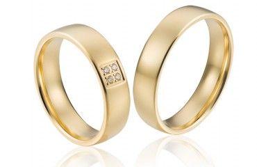 Brede  trouwringen van goud met een klassieke vleug en in de damesring 4 glinsterende briljanten.