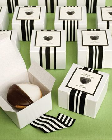 Boxed black-and-white cookies topped with thumbprint heart labels and graphic ribbon as wedding favors