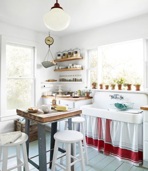 When the goal is rustic simplicity, there's no need to spend tons on custom cabinetry and granite counters. Paint transformed oak cabinets, bought off the rack at Lowe's and topped with Ikea's birch slabs, while the same white semigloss brightened stools from Walmart. An old tablecloth was used as a skirt for the farmhouse sink, and classic glass cannisters, also Walmart finds, were used for storage instead of upper cabinets.