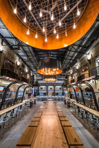 The Forks Market Food Hall - Exterior - The food court renovation was heavily inspired by the industrial past of the building, including industrial materials such as naked steel beams and trusses, and details such as the use of LED Edison bulbs.