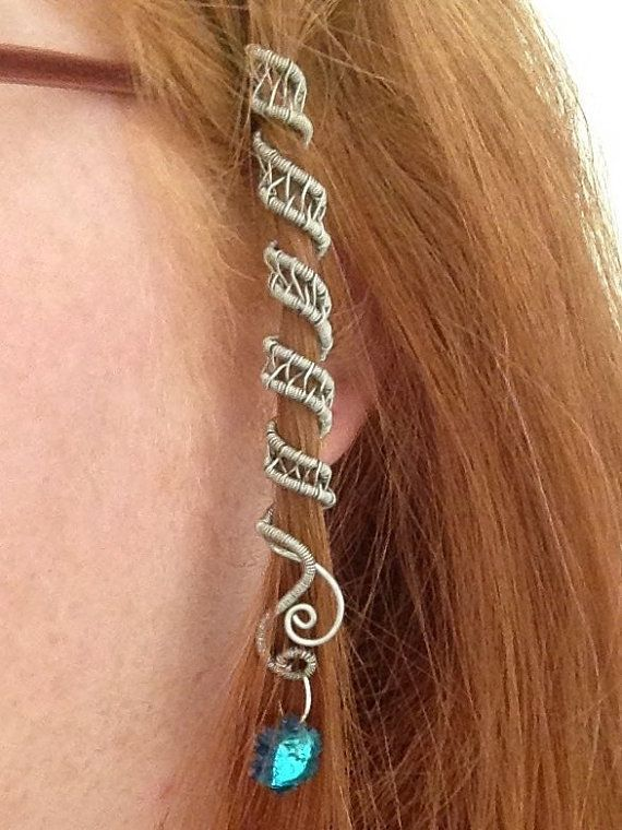 "This is a steel wire woven spiral that comfortably wraps around your hair. It has a lovely blue green snowflake charm dangling from the end of it.  Great for any hair, especially around dreads or braids. I'm calling these ""FairyTails""."
