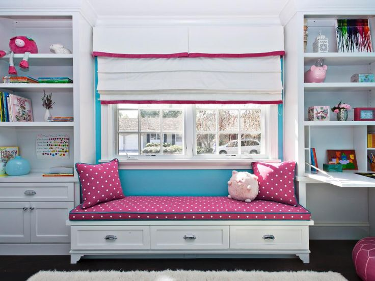 In this girl's bedroom, a window seat with a pink-and-white polka dot cushion and matching pillows pops against the blue wall. Two large built-in shelving units provide plenty of storage for books and toys.