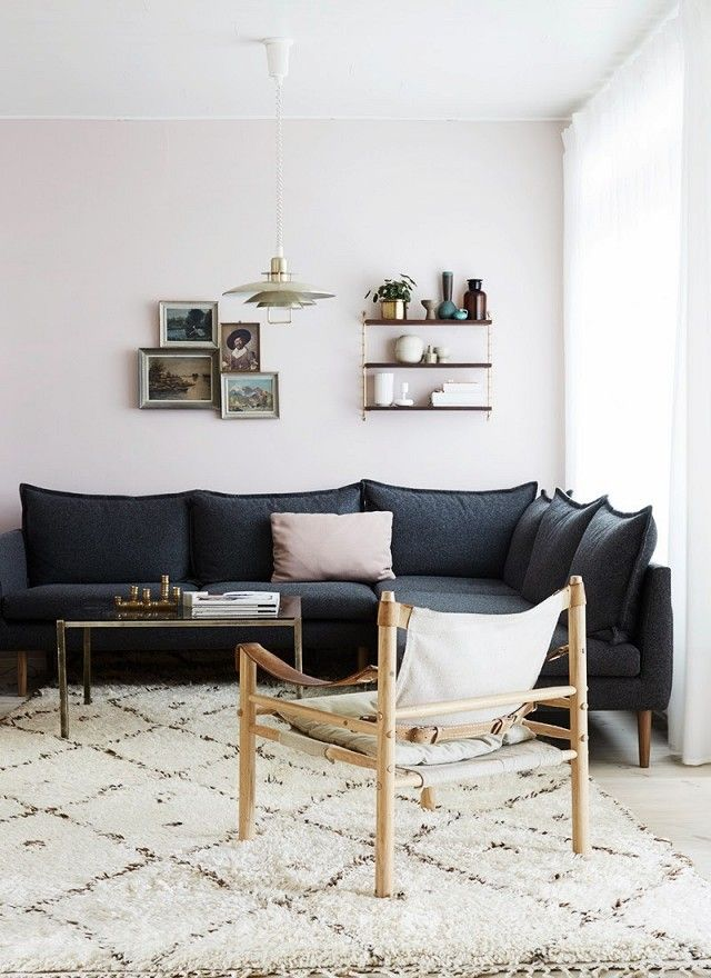 Living room with blush walls, a dark gray sectional, and a retro gold pendant light