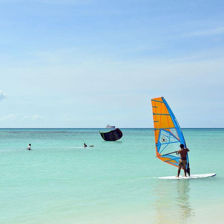Esta praia de #Aruba é conhecida por vários nomes #MooMba #Beach #Hadicurari Beach Fishermans Hut. fica bem próxima de Palm Beach ao lado do The Ritz-Calrton e é o point de encontro dos praticantes de #kitesurfing e #windsurfe. O colorido das velas deixa ainda mais linda esta que é uma das mais calmas praias de Aruba calma no sentido de quantidade de turistas porque aqui o vento sopra forte. O skyline com os resorts ao fundo deixam as fotos de Fishermans Hut lindas recomendamos seguir…