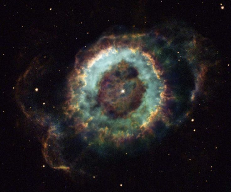 """Little Ghost Nebula. (NGC 6369) (Credit: Hubble Heritage Team, NASA) A planetary nebula in the constellation Ophiucus over 2000 light years away. William Herschel discovered it in the18th century. It's round like a planet, but was actually formed from material ejected by a dying star. What remains of the star is the white dwarf near the center. The nebula's main ring structure is about a light-year across. Mona Evans, """"Nebulae"""" http://www.bellaonline.com/articles/art43407.asp"""