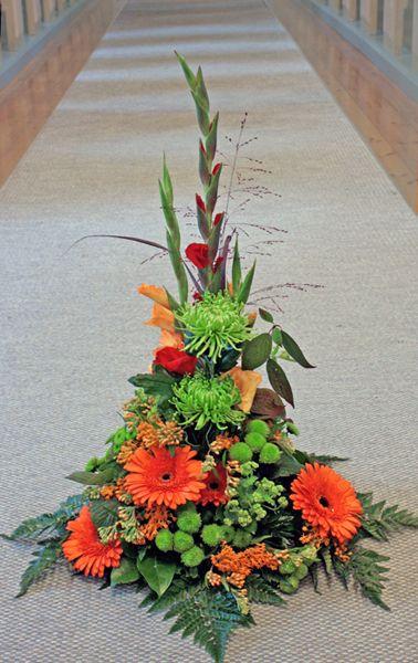 Hög sorgdekoration i orange och grönt. Gladiolus, chrysanthemum, gerbera, santini...