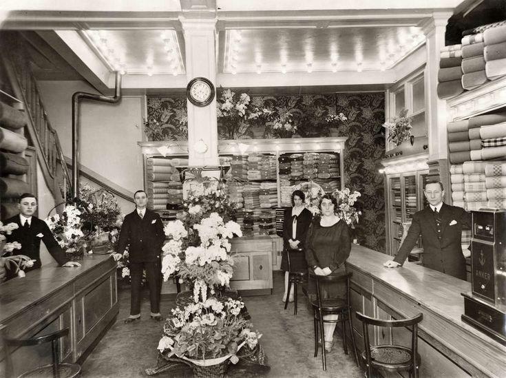 Interieur van luxe stoffenwinkel de stoffenkoning van H. van Dam in Amsterdam, met het personeel poserend in de winkel. Nederland, 1928.
