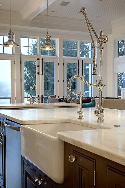 Classic, stunning pot filling faucet and sink in the kitchen island.  From a 4-story Craftsman style home construction by Lavallee Construction, discovered on Porch.com