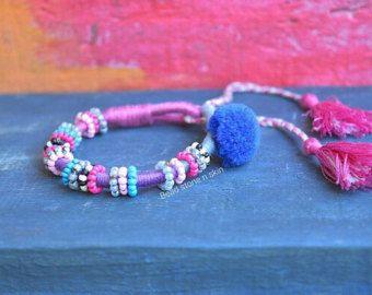 Questo braccialetto è coperto con anelli perla poco in molti colori. Un lato è rifinito con un pulsante di Kuchi depoca e una nappina di perle. È decorato con una campana di ottone indiano ed è regolabile per adattarsi maggior parte dei polsi. Si riceverà un braccialetto simile di quello che vedete nella foto.