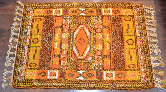 The colors and the patterns on this gorgeous vintage Moroccan Wool rug are absolutely STUNNING. Such a fun color pallet with a look that that can cross so man styles. Boho, midcentury, tribal, southwestern.. it goes on and on! It really is one of a kind!  This rug has original stickers or certification on the back identifying it as 100% wool and moroccan made. This rug has been well worn. The high pile has time worn wear which is visible in the pictures. Two of the braided tassels are…