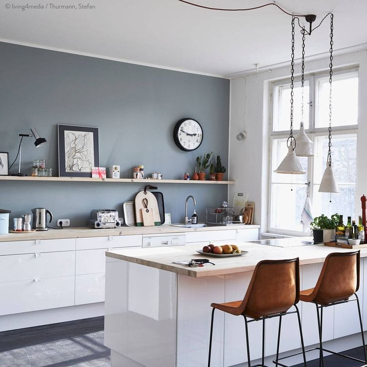 Grey wall with white cabinets and warm brown chairs. Crisp and clean.