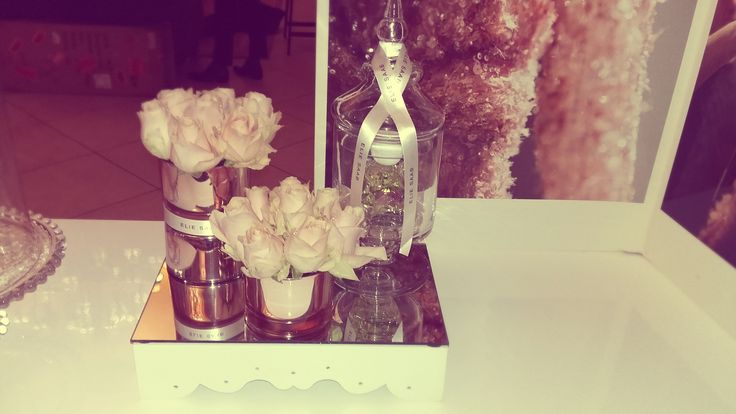 Perfume and flower display on the Elie Saab Perfume stand, using blush pink roses and rose gold candleholders