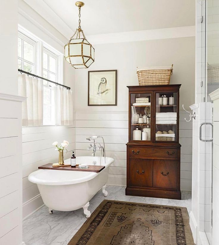 Vintage glass-front chest adds charm along with cafe curtains and claw footed tub.