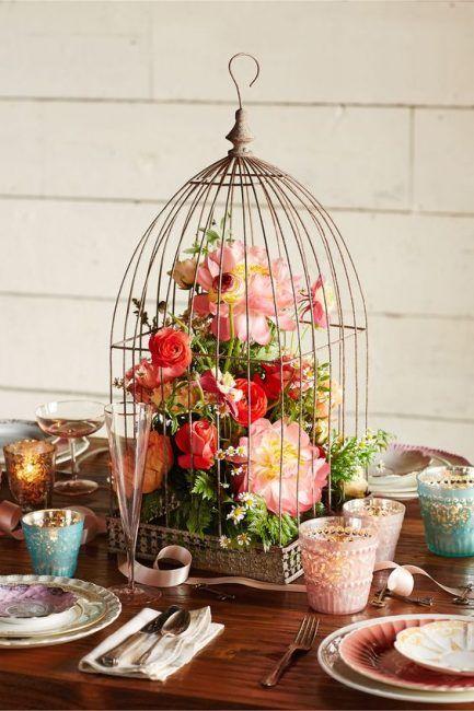 Decorar el centro de mesa con una jaula de pájaros