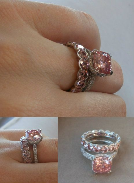 peachy pink moissanite cushion and platinum engagement ring and wedding band.  Joseph Schubach Jewelers. Mossanite  pink is always so perfect. its such a great alternative to pink sapphire. and can i just say i am officially obsessed with the wedding band being pink and in a diff style while the band on the engagement ring is diamond.