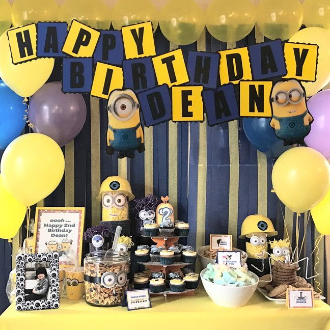 Minion birthday sweet bar and food names. Blue and yellow streamer backdrop. Minion centerpieces.