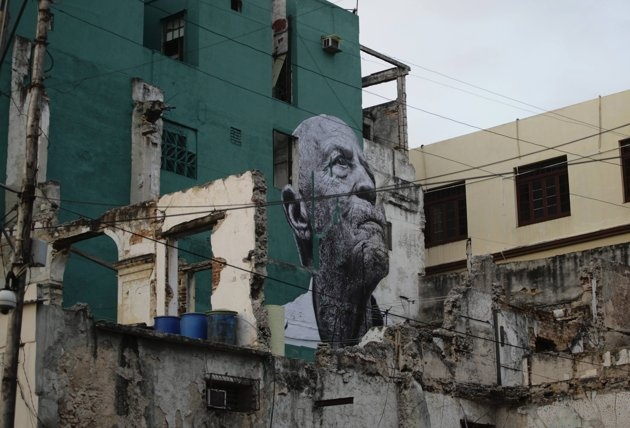"A creation by Cuban-American artist Jose Parla and French artist JR is seen on a wall in Havana for the upcoming 11th Biennial contemporary art exhibition May 10, 2012. The title of the project is ""Wrinkles Of The City"" where French artist JR's pictures of Cuban elderly people of the neighbourhood are combined with Parla's calligraphic messages and pasted on walls around the city."