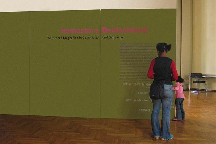 Konzeption der Ausstellung / ›Homestory Deutschland‹ ist ein kollektives Selbstporträt. Es greift afrikanische, afrikanisch amerikanische und Schwarze deutsche Erinnerungstraditionen auf, in denen der mündlichen und schriftlichen Weitergabe von gelebter Erfahrung eine maßgebliche Rolle zukommt. Schwarze Perspektiven und Reflexionen, Beiträge und Verdienste erfahren dabei als Quelle eines vielstimmigen und gemeinschaftlichen Wissens eine besondere Würdigung.