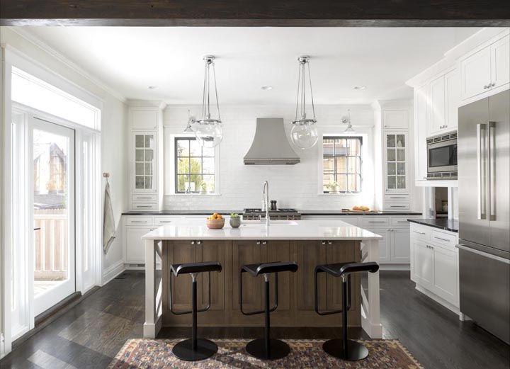 White Brick Backsplash chic kitchen features white perimeter cabinets paired with black