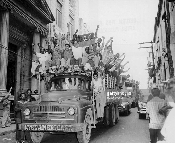 Trucks carry crowds celebrating the removal of dictator Fulgencio Batista and the arrival of Fidel Castro's 'July 26th Movement,' Havana, Cuba.