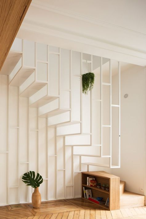 A white metal-framed staircase connects the two floors of this Parisian apartment