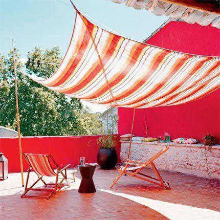Terrasse rouge avec un dais en toile rayée et des transats en bois (Velum)