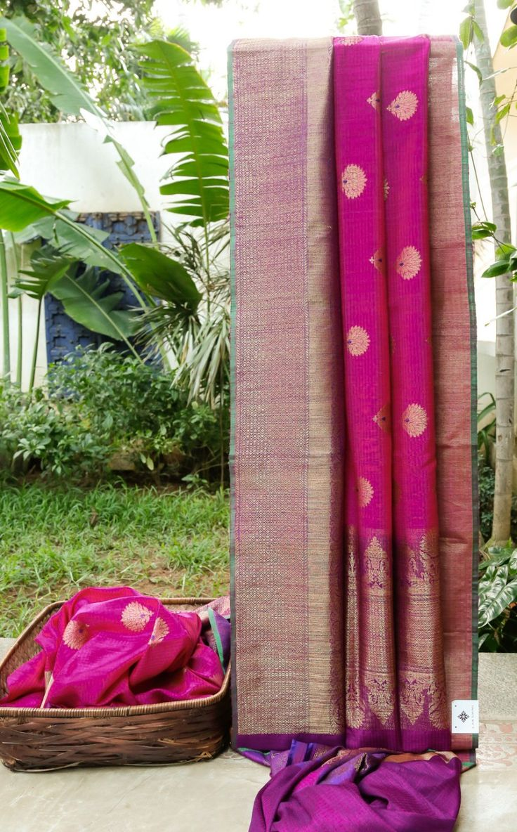 This Benares tussar has punch pink and magenta stripes with gold zari bhuttas and berry pink thread work. The border is in magenta, violet with gold zari while the pallu is in violet enmeshed with …