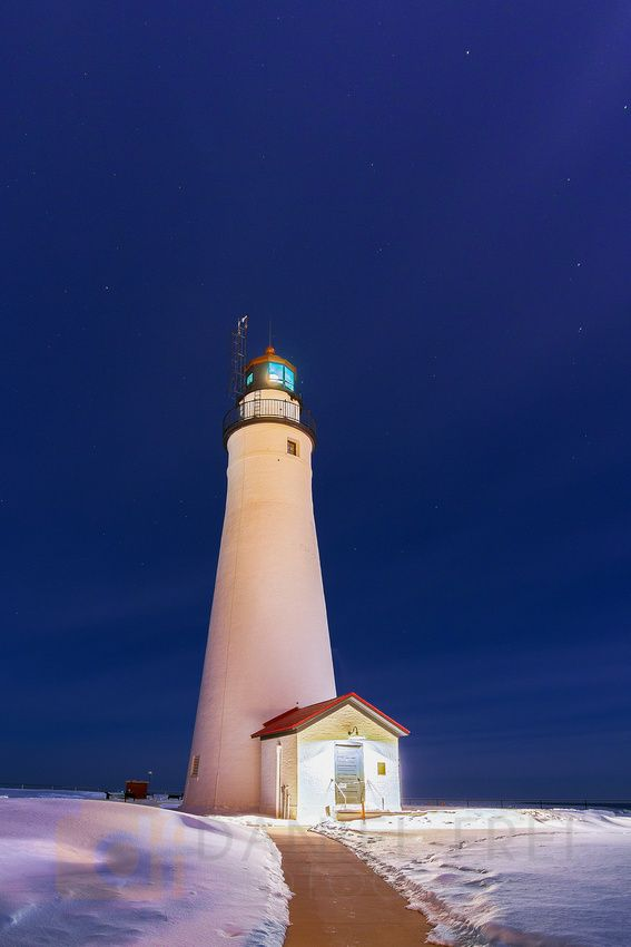Winter at Fort Gratiot Lighthouse in Port Huron, Michigan under the light of a full moon.