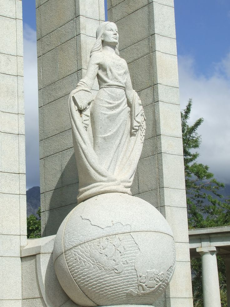 The central female figure, personifies religious freedom with a bible in her one hand and broken chain in the other. She is casting off her cloak of oppression and her position on top of the globe shows her spiritual freedom. The fleur-de-lis on her robe represents a noble spirit and character.