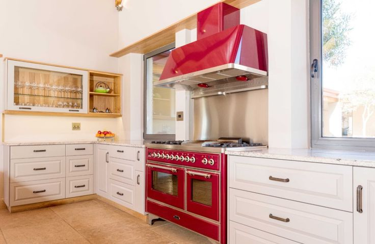 The burgundy Ilve Majestic duel fuel stove is a focus point in the kitchen dining room.