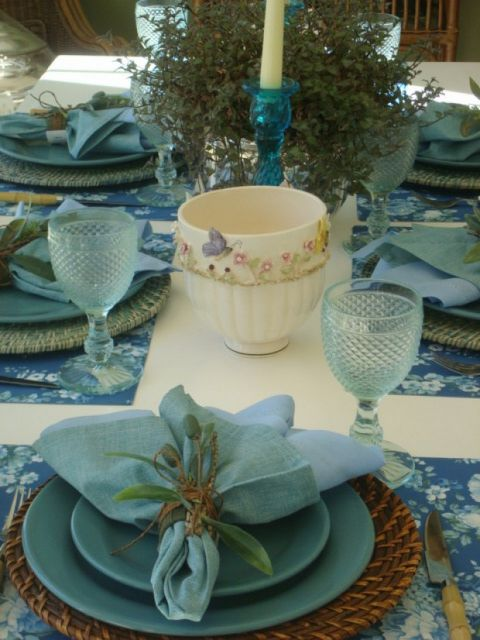Lovely dusty turquoise tablescape, using minimal pattern and an organic straw charger.  Flowers in napkin bundle are a nice touch.  The delicate pale turquoise wine glasses are gorgeous.