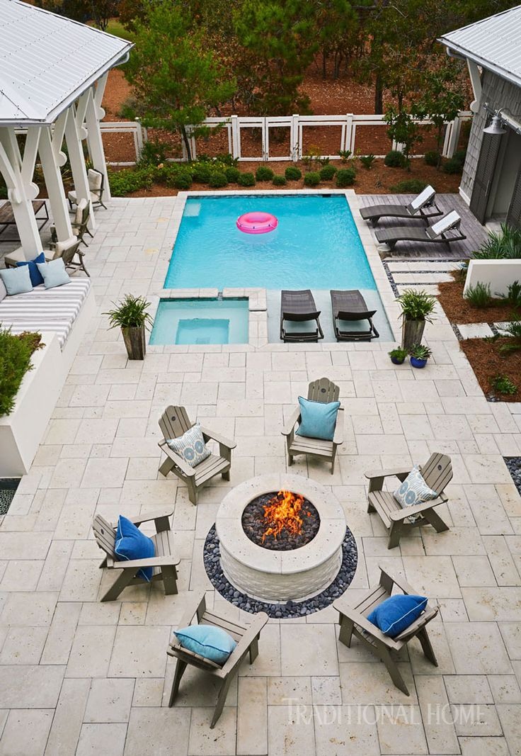 The pool, outfitted with comfy chaise longues from Frontgate, is surrounded by a series of outdoor rooms.