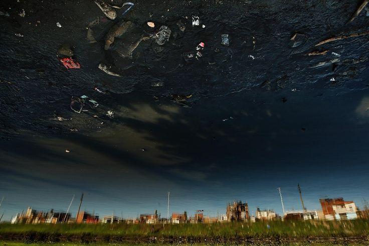 Casas de Villa Fiorito se ven reflejadas en las aguas del Riachuelo. La Cuenca Matanza Riachuelo es una de las más contaminadas del mundo. (Hernan Zenteno/muestra ARGRA)