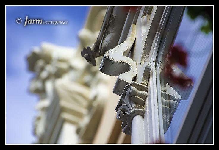 https://flic.kr/p/AAkVSx   Modernismo al detalle   Volvemos a mostrar un detalle del modernismo que podemos contemplar a pie de calle. A veces hace falta mirar un rato para darse cuenta de determinados detalles que complementan el conjunto de un edificio.  En este caso se puede apreciar claramente el detalle en madera del Coup de Fouet que he comentado otras veces, esa forma ondulada a modo de golpe de látigo. La diferencia con otras decoraciones florales de otras épocas radica en el grosor…