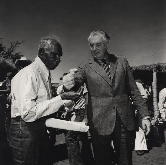 Mervyn Bishop (Australian, b.1945)  Prime Minister Gough Whitlam Pours Soil Into The Hand Of Traditional Land Owner Vincent Linginari, 1975/c1991. Silver gelatin photograph, titled, dated (twice) and signed in pencil verso, 30.8 x 30.3cm. Slight crinkles to image, tear to lower margin and minor wear to edges.   Bishop was commissioned by the Department Aboriginal Affairs to document this historic event of handing back the land to the Indigenous people.
