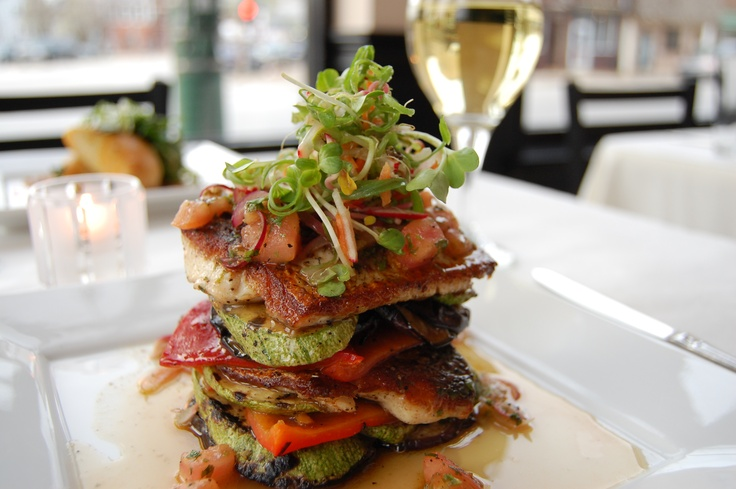 looks like red bell pepper, tomato, zucchini stacked with pan grilled fish topped with green onion and radish sprouts