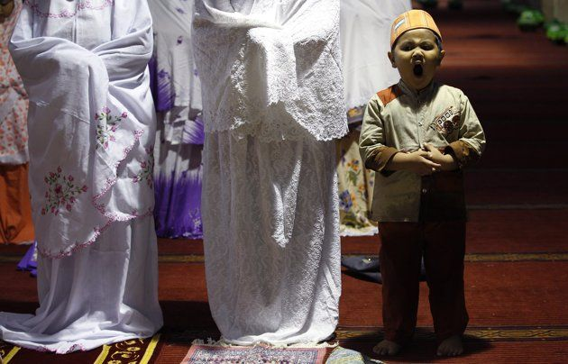 A boy yawns during an evening mass prayer session to mark the holy fasting month of Ramadan in Jakarta