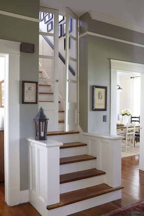 """""""The doors in the stairway with wavy glass are original to the house and point to the functionality designers favored in the 1920s. They keep the cooling and heating regulated between the downstairs and the two bedrooms and bath upstairs."""""""