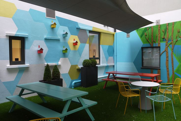 Shand House, Cardiff – transformation of communal courtyard for student accommodation. The feature murals had a funky and vibrant look, incorporating fun elements from nature including, plywood tree trunks and brightly painted bird boxes.  #exteriormural #handpainted #educationmural