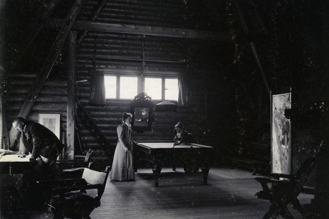 """Anders Zorn, Emma Zorn och Emilie Bartlett i Zorngården 1898. Två kvinnor spelar biljard. Emma och hans Älskarinna Emily. En man står lutad över ett skrivbord. Zorn har Bjudit in """"henne"""" till sin och Emmas stora Villa i Mora."""