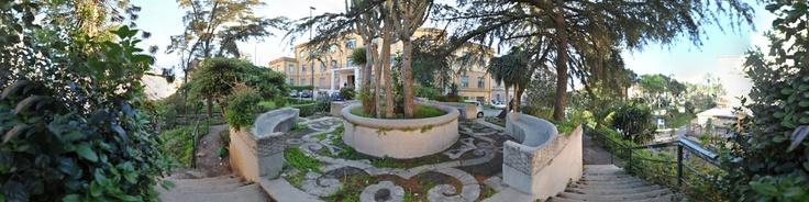 """Resti del Giardino dei Benedettini. I Benedettini fondarono l'indomani dell'eruzione del 1669 un 'Hortus' rustico sopra le lave. Da quel primo impianto poi sorse un immenso Orto Botanico ricco e complesso, tra specie rare, fontane, siepi, passeggi e terrazzamenti, tra alberi da frutta e piccole coltivazioni per il sostentamento. Tale Orto fu considerata una delle """"meraviglie"""" della città. L'Unità d'Italia ne d..."""