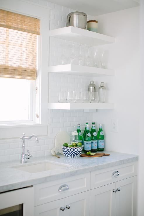 Kitchen bar area features a small wet bar sink and hook and spout faucet stands under a window next to stacked floating shelves filled with wine glasses and martini shakers. <br />