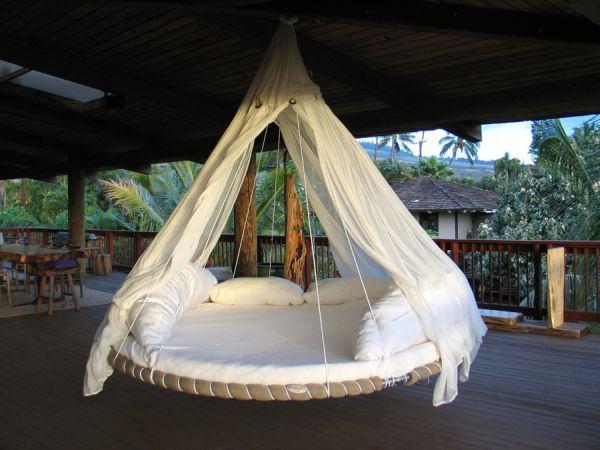 un lit rond et blanc suspendu par cordes avec un voilier fin et blanc