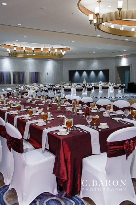 A beautiful wedding at the DoubleTree Houston Downtown with an Aggie flair. Event planning by the talented Krista with Event Identity, photography by C. Baron Photography. White spandex chair covers linen the royal head table with burgundy (aka maroon) taffeta sashes in a high crossover bow. Linens and ballroom chair treatments by House of Hough.