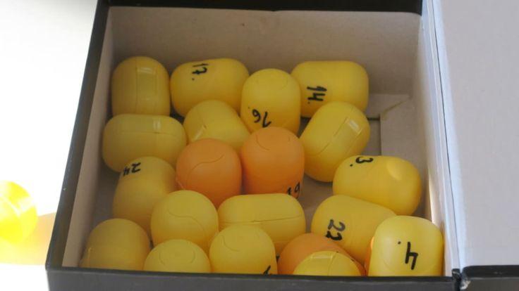 Numeroituja pääsiäismunayllätysten muovikoteloita laatikossa