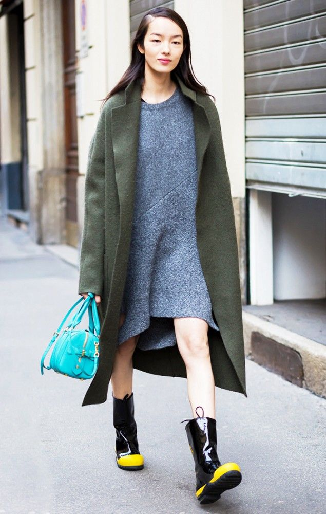 Fei Fei Sun wears a gray sweaterdress, olive green coat, rain boots, and a turquoise mini satchel