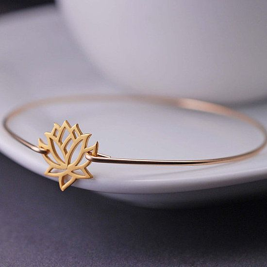 Gold Lotus Bangle Bracelet: This delicate gold lotus bangle bracelet ($40) will look great on its own or layered with other bangles and friendship bracelets.