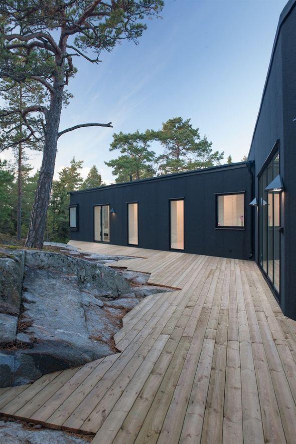 La nature environnante et la pente rocheuse du site ont dicté la forme de cette maison dont l'enveloppe extérieure est entièrement noire. Seules de nombreuses ouvertures vitrées viennent ponctuer les façades de zones claires, apporter lumière à l'intérieur et offrir de splendides vues sur la forêt.